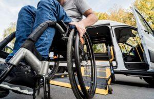 Foto de um homem cadeirante ao lado de um carro com as portas abertas e a rampa acionada.