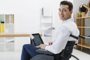 Foto de um homem cadeirante em uma sala de escritório e em seu colo está um laptop. Ele está olhando em direção à câmera.