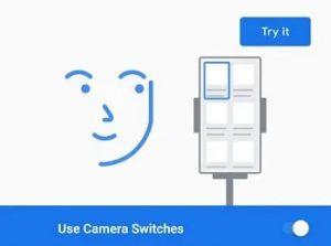 """Print do recurso Camera Switch do Android 12 com a ilustração lúdica de um rosto sorrindo ao lado de uma tela de celular. Há os textos em inglês: """"Try it"""" e """"Use Camera Switches""""."""