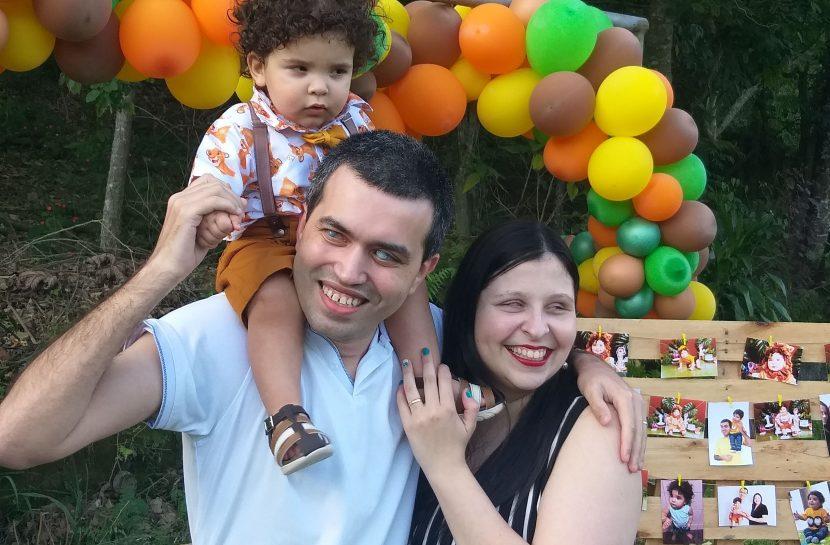 Foto do Leonardo, que está abraçado com a esposa, Camila, e tem, de cavalinho, sentado em seus ombros, o filho Gustavo. Atrás deles há um arco feito por bexigas coloridas e um mural de madeira com fotos variadas de vários momentos do Gustavo. O casal sorri.