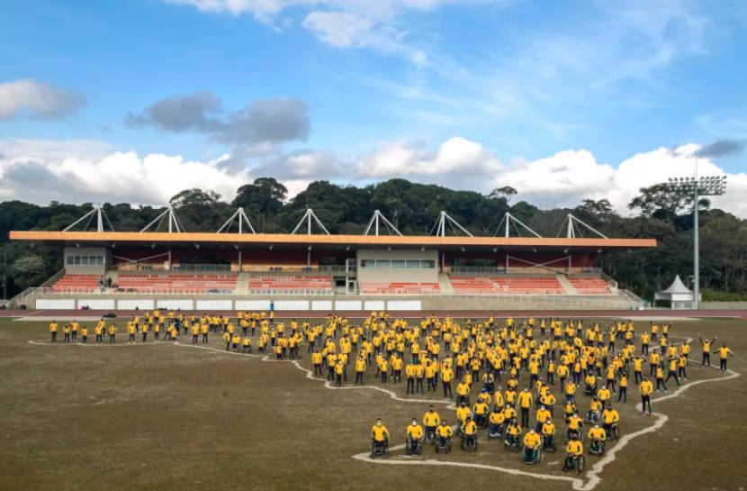 Dezenas de atletas paralímpicos do Brasil reunidos em um espaço aberto e vestem calças verdes e casacos amarelos, das cores da bandeira brasileira. Atrás, há uma arquibancada, com cadeiras vermelhas. No chão, está desenhado o contorno do mapa do nosso país.