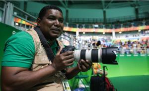 Foto de João Maia de perfil segurando uma máquina fotográfica nas mãos durante a cobertura dos Jogos Paralímpicos do Rio de Janeiro em 2016