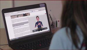 Foto de uma mulher de costas usando um laptop que está em sua frente e sobre uma mesa, nele está aberto um site e em seu lado direito há uma janela com um avatar intérprete de Libras