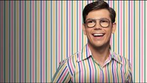 Imagem da série Special, da Netflix. O protagonista, Ryan, está sorrindo com os dentes à mostra. Ele olha de lado e usa óculos de grau estilo aviador, com hastes preta e branca. Ele veste uma camisa social branca com listras verticais azuis, rosas, amarelas e verdes, exatamente a mesma estampa do fundo da foto.