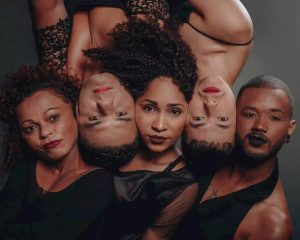 Foto tirada de cima pra baixo de 2 mulheres e 3 homens deitados no chão. Eles usam roupas pretas e maquiagem e estão lado a lado, intercalados.