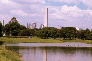 Foto paisagem do Parque do Ibirapuera. O céu está azul e com nuvens brancas, e há muitas árvores, grama e um lago no centro da imagem. Ao fundo, o Obelisco e Monumento Mausoléu ao Soldado Constitucionalista de 32.