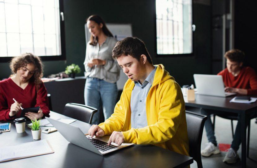 Foto de homem com síndrome de down em um escritório mexendo em um notebook (fonte: Halfpoint - iStock)
