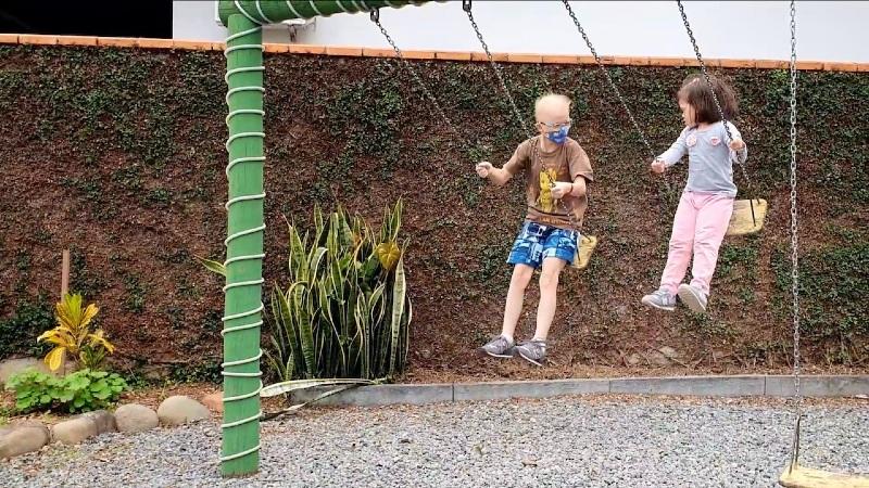 """Print de cena do filme nacional """"Fale Conosco"""", com duas crianças, um menino e uma menina, com síndrome de Down brincando em balanços"""