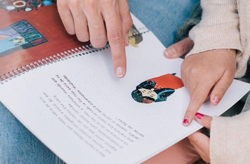 Foto em detalhe de livro infantil em Braille no colo de uma mulher, ao lado dela há uma garota. As duas tocam a página da publicação com a ponta dos dedos