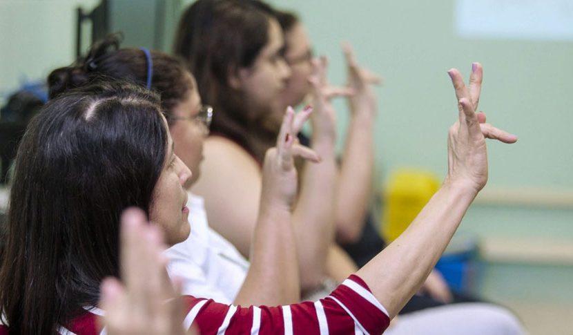 Foto de um grupo de mulheres sentadas de perfil sinalizando a letra F em Libras. Foto: Ricardo Amanajás/Agência Pará