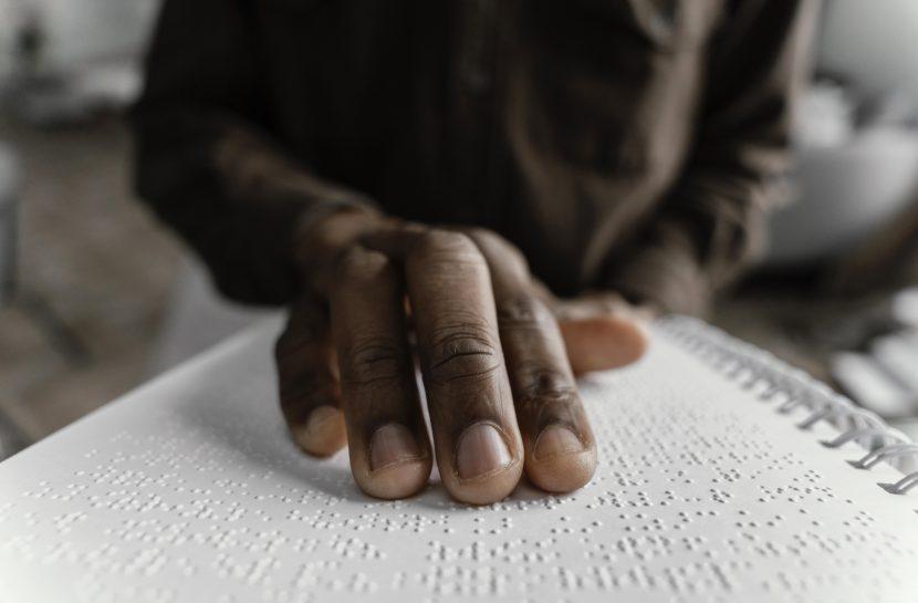 Foto em close de uma mão sobre página escrita em Braille