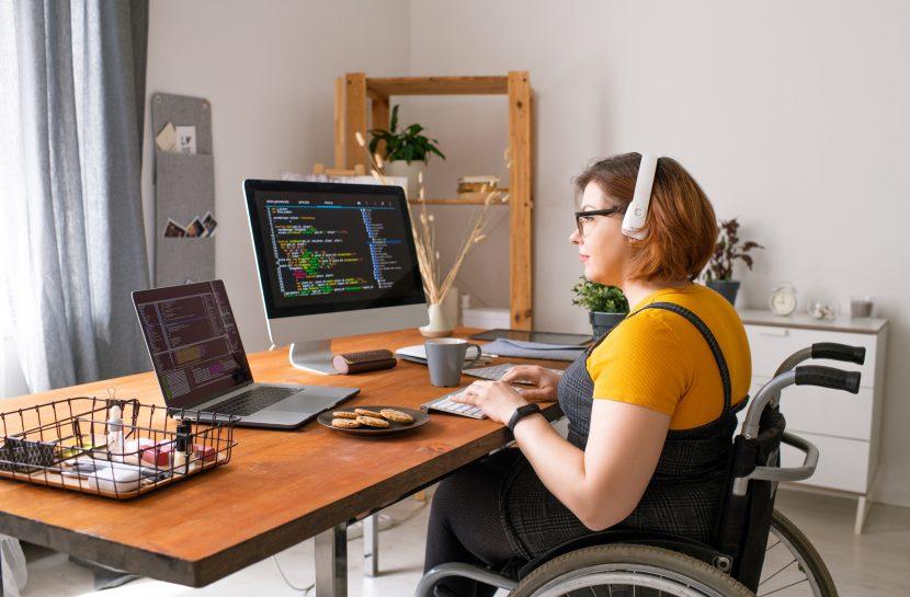 Foto de uma mulher cadeirante trabalhando com um computador e um laptop, na tela dos equipamentos há códigos de programação